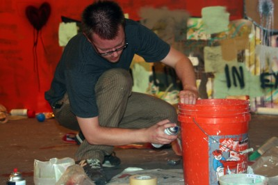 Derek painting a bucket in his studio.