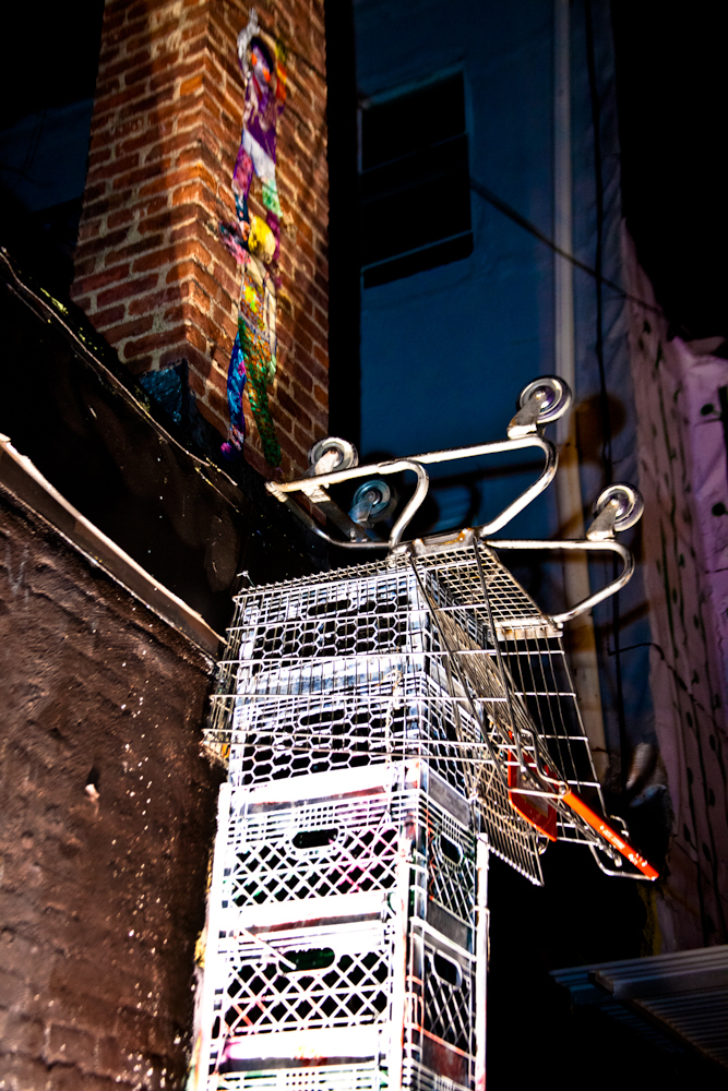 A scupture of crates and a shopping cart careens upward toward a wheatpaste by Various & Gould. © Vincent Cornelli